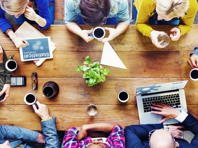 Office coffee: Employees gather for a meeting over a cup of coffee.