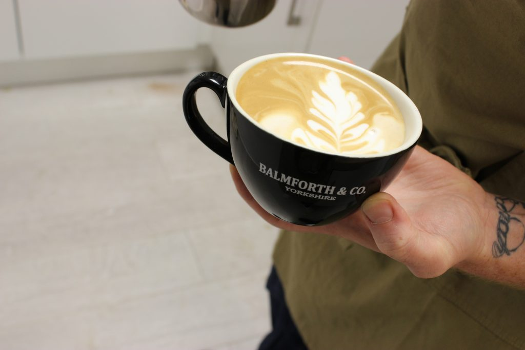 branded coffee cup with latte art for university catering